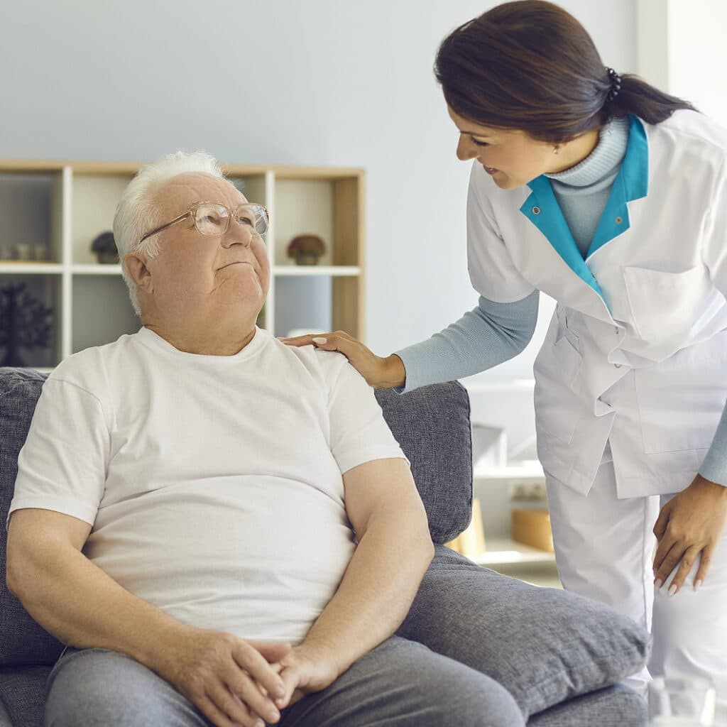 Friendly doctor or helpful nurse comes to see senior patient at home or in assisted living facility